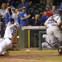 Photo - Chicago Cubs' John Baker, left, scores the game winning run off a sacrifice fly by Starlin Castro, as the ball gets past Colorado Rockies catcher Wilin Rosario (20) during the 16th inning of a baseball game Wednesday, July 30, 2014, in Chicago. The Cubs' won 4-3. (AP Photo/Charles Rex Arbogast)