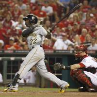 Photo - Pittsburgh Pirates' Andrew McCutchen follows through on a solo home run off Cincinnati Reds relief pitcher J.J. Hoover in the 11th inning of a baseball game, Saturday, July 12, 2014, in Cincinnati. Reds catcher Devin Mesoraco is at  right. The Pirates won 6-5 in 11 innings. (AP Photo/David Kohl)