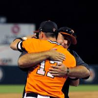 Photo - Oklahoma State pitcher head coach Josh Holiday, back, hugs left fielder Gage Green following the 6-4 Oklahoma State win over Fullerton in the NCAA college baseball regional tournament game in Stillwater, Okla, Sunday, June 1, 2014. Oklahoma State defeated Fullerton 6-4. (AP Photo/Brody Schmidt)