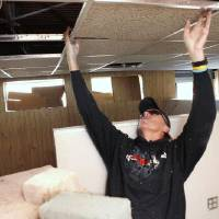 Photo - Randy Swanson installs ceiling tiles Saturday as members of Southern Nazarene University's class of 1980 work to help Love Link Ministries Inc. prepare to move into a new building in downtown Oklahoma City. PHOTO BY PAUL HELLSTERN, THE OKLAHOMAN <strong>PAUL HELLSTERN</strong>