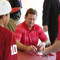 Photo - OU football head basketball coach Bob Stoops signs autographs for fans during the annual OU Sooner Caravan stop in Tulsa, Okla., taken on June 5,2014. JAMES GIBBARD/Tulsa World