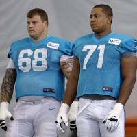 Photo - FILE - In this July 24, 2013, file photol, Miami Dolphins guard Richie Incognito (68) and tackle Jonathan Martin (71) stand on the field during NFL football practice in Davie, Fla. Martin, the offensive tackle at the center of the Dolphins' bullying scandal, has been traded to the San Francisco 49ers. The Dolphins announced the deal Tuesday night, March 11, 2014, on the first day of NFL free agency. Martin's move cross country brings him back to the Bay Area to be reunited with his former Stanford coach, Jim Harbaugh. (AP Photo/Lynne Sladky, File)