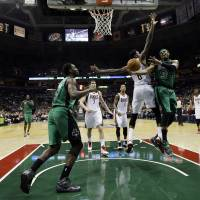 Photo - Boston Celtics' Paul Pierce (34) tries to drive to the basket past Milwaukee Bucks' Larry Sanders (8) during the first half of an NBA basketball game on Saturday, Dec. 1, 2012, in Milwaukee. (AP Photo/Morry Gash)