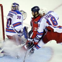 Photo -   Washington Capitals center Brooks Laich (21) gets caught between New York Rangers goalie Henrik Lundqvist (30) and defenseman Marc Staal (18) during the first period of Game 3 of their NHL hockey Stanley Cup second-round playoff series at the Verizon Center in Washington, Wednesday, May 2, 2012. (AP Photo/Susan Walsh)