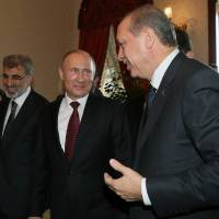 Photo - Russian President Vladimir Putin, center, and Turkey's Prime Minister Recep Tayyip Erdogan, right, speake before a meeting in Istanbul, Turkey, Monday, Dec. 3, 2012. Putin visits Turkey on a one-day trip expected to focus on economic issues as well as differing views over how to resolve the Syrian conflict. Turkish Energy Minister Taner Yildiz is at left.(AP Photo/Pool)