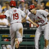 Photo - St. Louis Cardinals' Jon Jay (19) is greeted by Matt Carpenter as he scores in the seventh inning of a baseball game against the Pittsburgh Pirates on Monday, Aug. 25, 2014, in Pittsburgh. Jay scored from second behind Matt Carpenter on a single by Matt Holiday. (AP Photo/Keith Srakocic)
