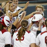 Photo - The OU team celebrates with Shelby Pendley as she crosses home after hitting a home run in the sixth inning of a Bedlam softball game between the University of Oklahoma and Oklahoma State University in Norman, Okla., Wednesday, April 2, 2014. Oklahoma won 2-0. Photo by Bryan Terry, The Oklahoman
