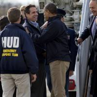 Photo -  President Barack Obama is greeted by New York Gov. Andrew Cuomo upon his arrival at JFK International Airport in New York Thursday, Nov. 15, 2012, before taking a aerial tour of damage along the New York coastline in the of Superstorm Sandy. From left are, New York City Mayor Michael Bloomberg, Housing and Urban Development Secretary Shaun Donovan, in HUD jacket, Cuomo, the president, Sen. Kirsten Gillibrand, D-N.Y., and Sen. Charles Schumer, D-N.Y. (AP Photo/Craig Ruttle)