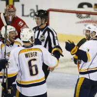 Photo - Nashville Predators' Matt Cullen, right, celebrates his goal with teammates Mike Fisher, left, and Shea Weber during the third period of an NHL hockey game against the Calgary Flames in Calgary, Alberta, Friday, March 21, 2014. The Predators won 6-5. (AP Photo/The Canadian Press, Jeff McIntosh)