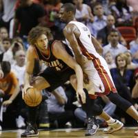 Photo - Portland Trail Blazers center Robin Lopez (42) drives up against Miami Heat center Chris Bosh (1) during the first half of an NBA basketball game, Monday, March 24, 2014 in Miami. (AP Photo/Wilfredo Lee)