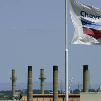 Photo - FILE - This April 21, 2008 file photo shows a Chevron flag flying over the Chevron refinery in Richmond, Calif. Chevron Corp. reports quarterly financial results before the market opens on Friday, April 26, 2013. (AP Photo/Ben Margot, File)
