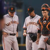 Photo - From left, San Francisco Giants pitching coach Dave Righetti confers with starting pitcher Ryan Vogelsong and catcher Buster Posey after Vogelsong gave up a three-run home run to Colorado Rockies' Wilin Rosario in the first inning of a baseball game in Denver on Monday, April 21, 2014. Vogelsong gave up a solo home run to the Rockies' Nolan Arenado as well in the inning. (AP Photo/David Zalubowski)