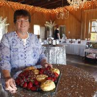 Photo -  Debbie Lowery, of Running Wild Catering, sets up for an event on July 21 at the Red Barn at Waldo's Pond. Photo by David McDaniel, The Oklahoman   David McDaniel -  The Oklahoman