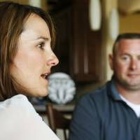 Photo - Jennifer Douglas speaks during an interview as her husband, Brandon Douglas, listens at their home in Oklahoma City, Monday, July 1, 2013. Brandon Douglas left the Marines as a Gunnery Sergeant after battling PTSD. Photo by Nate Billings, The Oklahoman