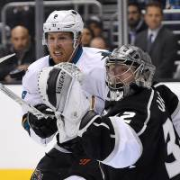 Photo - Los Angeles Kings goalie Jonathan Quick, right, is scored on by San Jose Sharks right wing Brent Burns as center Joe Pavelski looks on during the first period in Game 3 of an NHL hockey first-round playoff series , Tuesday, April 22, 2014, in Los Angeles. (AP Photo/Mark J. Terrill)