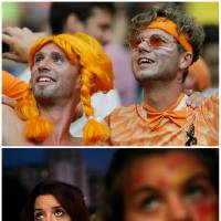 Photo - In this combination of Associated Press photos Dutch soccer fans, top, celebrate in Salvador, Brazil and Spanish soccer fans, bottom, in Madrid, watch on a giant display as the Netherlands defeat Spain during a World Cup soccer match Friday, June 13, 2014. (AP Photo)