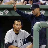 Photo - FILE - In this Sept. 13, 2013 file photo, New York Yankees' Alex Rodriguez sits in the dugout as Derek Jeter stands next to him during the first inning of a baseball game against the Boston Red Sox at Fenway Park in Boston.  Rodriguez's drug suspension has been cut to 162 games from 211 by arbitrator Fredric Horowitz, a decision sidelining the New York Yankees third baseman the entire 2014 season.  (AP Photo/Elise Amendola)