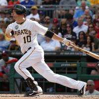 Photo - Pittsburgh Pirates' Jordy Mercer (10) drives in two runs with a single off Philadelphia Phillies starting pitcher Roberto Hernandez during the first inning of a baseball game in Pittsburgh, Friday, July 4, 2014. (AP Photo/Gene J. Puskar)