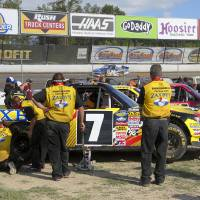 Photo - Crews watch from the pits as Ryan Blaney, backbround, runs a qualifying lap for the inaugural Mudsummer Classic NASCAR Trucks Series auto race at Eldora Speedway, Wednesday, July 24, 2013, in Rossburg, Ohio. (AP Photo/The Dayton Daily News, Greg Lynch)  LOCAL PRINT OUT; LOCAL TV OUT; WKEF-TV OUT; WRGT-TV OUT; WDTN-TV OUT
