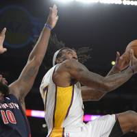 Photo - Los Angeles Lakers center Jordan Hill, right, puts up a shot as Detroit Pistons forward Greg Monroe defends during the first half of an NBA basketball game, Sunday, Nov. 17, 2013, in Los Angeles. (AP Photo/Mark J. Terrill)
