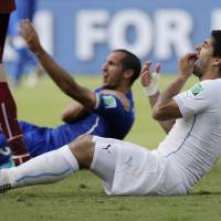 Photo - FILE - In this June 24, 2014 file photo, Uruguay's Luis Suarez holds his teeth after biting Italy's Giorgio Chiellini's shoulder during the group D World Cup soccer match between Italy and Uruguay at the Arena das Dunas in Natal, Brazil. On Thursday, June 26, 2014, FIFA banned Suarez for 9 games and 4 months for biting his opponent at the World Cup. (AP Photo/Ricardo Mazalan, File)