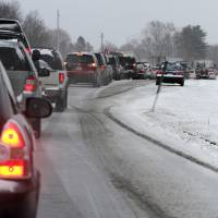 Photo - Cars are stuck in traffic as a winter storm arrives , Friday, Feb. 8, 2013 in Newington, N.H. Snow began to fall around the Northeast on Friday at the start of what's predicted to be a massive, possibly historic blizzard, and residents scurried to stock up on food and supplies ahead of the storm. (AP Photo/Jim Cole)