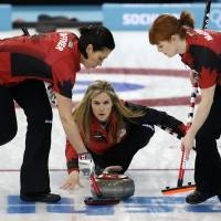 Photo - Canada's skip Jennifer Jones, center, delivers the rock to her sweepers Jill Officer, left, and Dawn McEwen during women's curling competition against Great Britain at the 2014 Winter Olympics, Wednesday, Feb. 12, 2014, in Sochi, Russia. (AP Photo/Robert F. Bukaty)