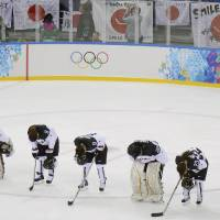 Photo - Members of Team Japan bow after their 4-0 loss to Germany in the 2014 Winter Olympics women's ice hockey game at Shayba Arena, Thursday, Feb. 13, 2014, in Sochi, Russia. (AP Photo/Matt Slocum)