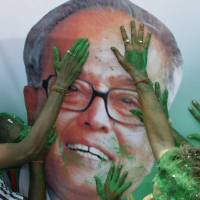 Photo -   Activists of India's ruling Congress party apply colored powder on portrait of Pranab Mukherjee, as they celebrate his victory in India's presidential election in Kolkata, India, Sunday, July 22, 2012. Former Finance Minister Pranab Mukherjee, the candidate from India's governing Congress party, has claimed victory in the election for the country's next president, a largely ceremonial position. His rival, Purno Agitok Sangma, conceded defeat. (AP Photo/Bikas Das)