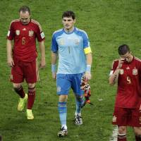 Photo - Spain's Andres Iniesta, goalkeeper Iker Casillas and Fernando Torres, from left, leave the pitch after the group B World Cup soccer match between Spain and Chile at the Maracana Stadium in Rio de Janeiro, Brazil, Wednesday, June 18, 2014.  Spain was eliminated from World Cup contention with a 2-0 loss to Chile.  (AP Photo/Christophe Ena)