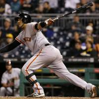 Photo - San Francisco Giants' Hector Sanchez drives in teammate Buster Posey with a single off Pittsburgh Pirates relief pitcher Tony Watson during the seventh inning of a baseball game in Pittsburgh Monday, May 5, 2014. (AP Photo/Gene J. Puskar)