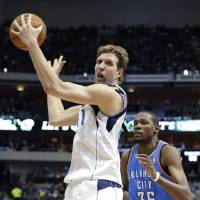 Photo - Dallas Mavericks forward Dirk Nowitzki turns against a defending Oklahoma City Thunder forward Kevin Durant (35) during the first half of an NBA basketball game Tuesday, March 25, 2014, in Dallas. (AP Photo/LM Otero)