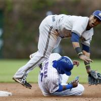 Photo - Milwaukee Brewers shortstop Jean Segura forces out Chicago Cubs' Luis Valbuena while turning a double play during the third inning of a baseball game on Friday, May 16, 2014, in Chicago. (AP Photo/Andrew A. Nelles)
