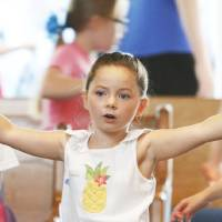 Photo - Lauryn Lackey, 5, flaps her arms in a flying motion while singing during the opening of Vacation Bible School with the theme