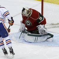 Photo - Edmonton Oilers left wing Taylor Hall (4) scores on Minnesota Wild goalie Darcy Kuemper during tje shootout of in NHL hockey game in St. Paul, Minn., Tuesday, March 11, 2014. Edmonton won 4-3. (AP Photo/Ann Heisenfelt)
