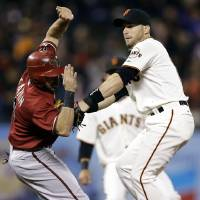 Photo -   San Francisco Giants second baseman Marco Scutaro, right, tags out Arizona Diamondbacks' Adam Eaton after a ground ball from Aaron Hill during the first inning of a baseball game, Wednesday, Sept. 26, 2012, in San Francisco. Scutaro then threw to first base to complete a double play. (AP Photo/Marcio Jose Sanchez)