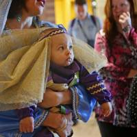 Photo - April Ghassemi holds Esther Assef, 11 months, during a Purim carnival at Temple B'nai Israel.