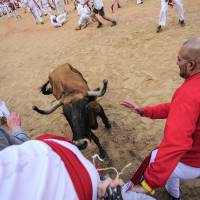 Photo - Revelers try to protect against a bull on the bull ring, at the San Fermin festival, in Pamplona, Spain, Tuesday, July 8, 2014. Revelers from around the world in Pamplona take part in an eight-day event of the running of the bulls glorified by Ernest Hemingway's 1926 novel