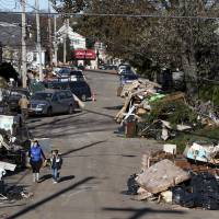 Photo -   Garbage lies piled on the street in the New Dorp neighborhood of Staten Island, N.Y., Sunday, Nov. 4, 2012, in the aftermath of Superstorm Sandy. (AP Photo/Seth Wenig)