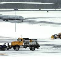 Photo - FILE - In this Thursday, Dec. 27, 2012 file photo, snow is cleared on a runway as a plane taxis into Manchester-Boston Regional Airport in Manchester, N.H. As the Northeast braces for its largest winter storm in more than a year, airlines are already employing a strategy that has served them well in recent years: Cancel flights early and keep planes, crews and passengers away from snowed-in airports. (AP Photo/Elise Amendola, File)