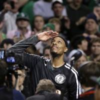 Photo - Brooklyn Nets forward Paul Pierce, center, formerly of the Boston Celtics, salutes the crowd during a tribute to him in the first half of an NBA basketball game against the Boston Celtics, Sunday, Jan. 26, 2014, in Boston. (AP Photo/Steven Senne)
