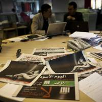 """Photo - Egyptian journalists at the editorial room of Al-Masry Al-Youm daily newspaper next to copies of Egypt's most prominent newspapers running black background front pages with Arabic that reads, """"no to dictatorship, tomorrow free newspapers will obscure to protest the freedom's restrictions,"""" and a picture of a man wrapped in newspapers with his feet cuffed, in Cairo, Egypt, Monday, Dec. 3, 2012. Eleven Egyptian newspapers are planning to suspend publication on Tuesday to protest against President Mohammed Morsi's decision to call a constitution referendum on 15 December. (AP Photo/Nasser Nasser)"""