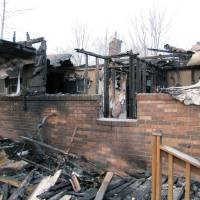 Photo - This photo shows the charred remains of  a home after a fire erupted, Saturday, March 9, 2013 in Gray, Ky. Fire erupted Saturday at a rural Kentucky home, killing two adults and five children inside, a coroner said. Knox County Coroner Mike Blevins said Saturday afternoon that the adult victims found inside the ranch-style home were a woman and her boyfriend. The woman was the mother of three of the children who died, while two other children were from another family, he said. (AP Photo/The Lexington Herald-Leader, Bill Estep)