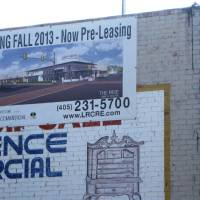Photo - An old sign promising an opening of The Rise in fall 2013 is still displayed on the building's west facade.  Photo by Steve Lackmeyer, The Oklahoman