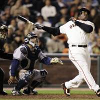 Photo - FILE - In this Aug. 24, 2007, file photo, San Francisco Giants' Barry Bonds, right, hits his 761st career home run, a solo effort, off Milwaukee Brewers pitcher Chris Capuano in the fourth inning of a baseball game in San Francisco. Bonds, Roger Clemens and Sammy Sosa are set to show up on the Hall of Fame ballot for the first time on Wednesday, Nov. 28, 2012, and fans will soon find out whether drug allegations block the former stars from reaching baseball's shrine. (AP Photo/Marcio Jose Sanchez, File)