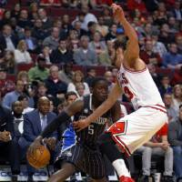 Photo - Orlando Magic guard Victor Oladipo, left, is guarded by Chicago Bulls center Joakim Noah, right, during the first half of an NBA basketball game Monday, April 14, 2014, in Chicago.  (AP Photo/Jeff Haynes)