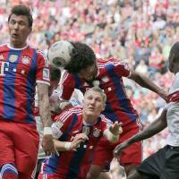 Photo - Bayern's Mario Mandzukic of Croatia, from left, teammate Dante and Bastian Schweinsteiger challenge for the ball during the German first division Bundesliga soccer match between FC Bayern Munich and VfB Stuttgart, in Munich, southern Germany, Saturday, May 10, 2014. (AP Photo/Matthias Schrader)