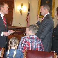 Photo - Rep. James Lankford, left, delivers a ceremonial oath of office on Capitol Hill on Thursday to new Rep. Markwayne Mullin, who was accompanied by his family.  Chris Casteel - The Oklahoman