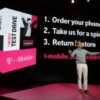 Photo - T-Mobile Chief Marketing Officer Mike Sievert talks about his company's new program that offers a free seven-day test drive of an Apple iPhone 5S at T-Mobile's Uncarrier 5.0 event, Wednesday, June 18, 2014, in Seattle. (AP Photo/Ted S. Warren)