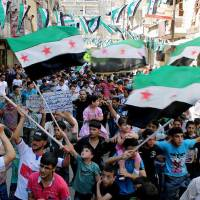 Photo - This citizen journalism image provided by Aleppo Media Center AMC which has been authenticated based on its contents and other AP reporting, shows anti-Syrian regime protesters holding Syrian revolution flags, during a demonstration in the neighborhood of Bustan Al-Qasr in Aleppo, Syria, Friday, June 28, 2013. Intense shelling by Syrian government troops on a village in the country's south killed several women and girls overnight as forces loyal to President Bashar Assad pushed ahead with an offensive against rebels near the border with Jordan, activists said Friday. (AP Photo/Aleppo Media Center AMC)
